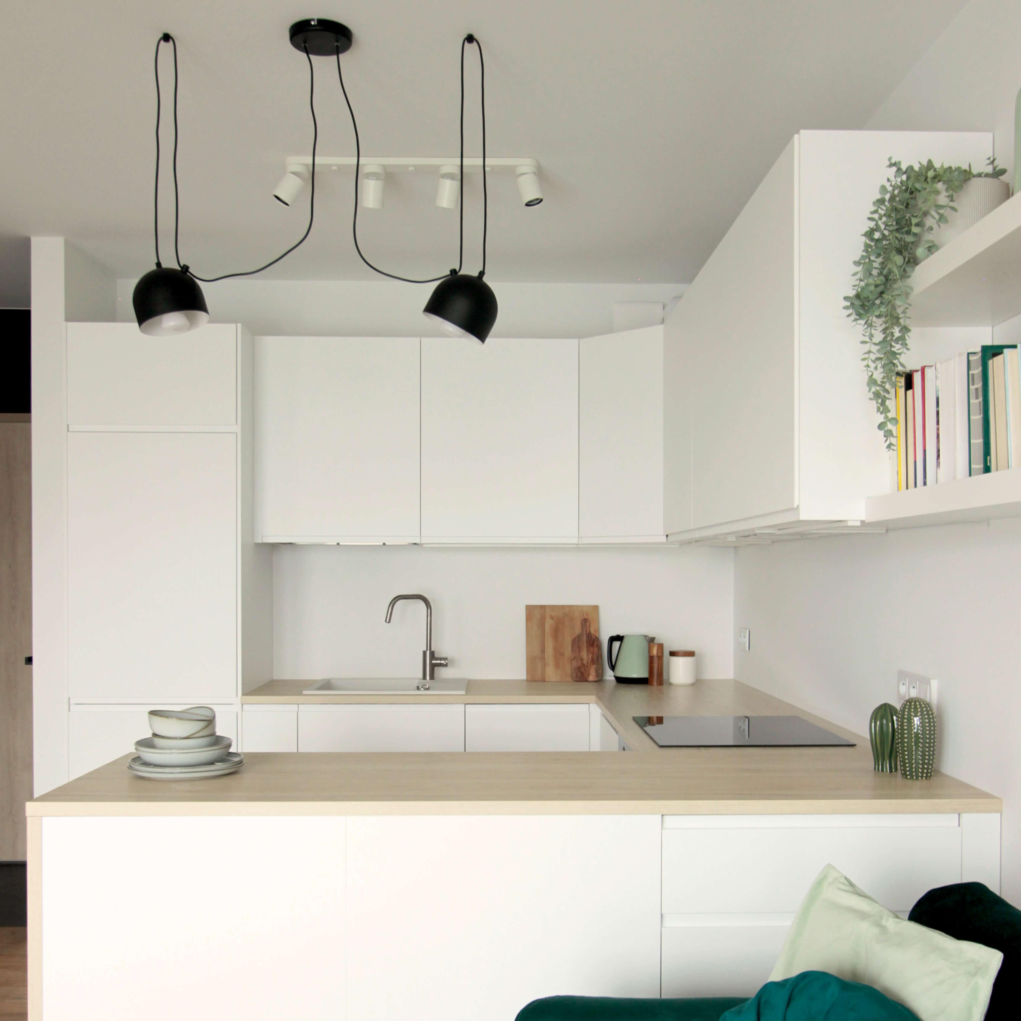 Projekt wnętrza mieszkania wraz z nadzorem nad realizacją. Aneks kuchenny w mieszkaniu 39 m2. Aneksy kuchenne w salonach to często spotykane rozwiązanie. Dzięki wyspie kuchennej ta strefa bardzo jasno oddziela się od pozostałych. Zabudowa w kształcie litery U pozwala wygodnie gotować zapewniając odpowiednią kolejność sprzętów i dużą ilość blatu roboczego.