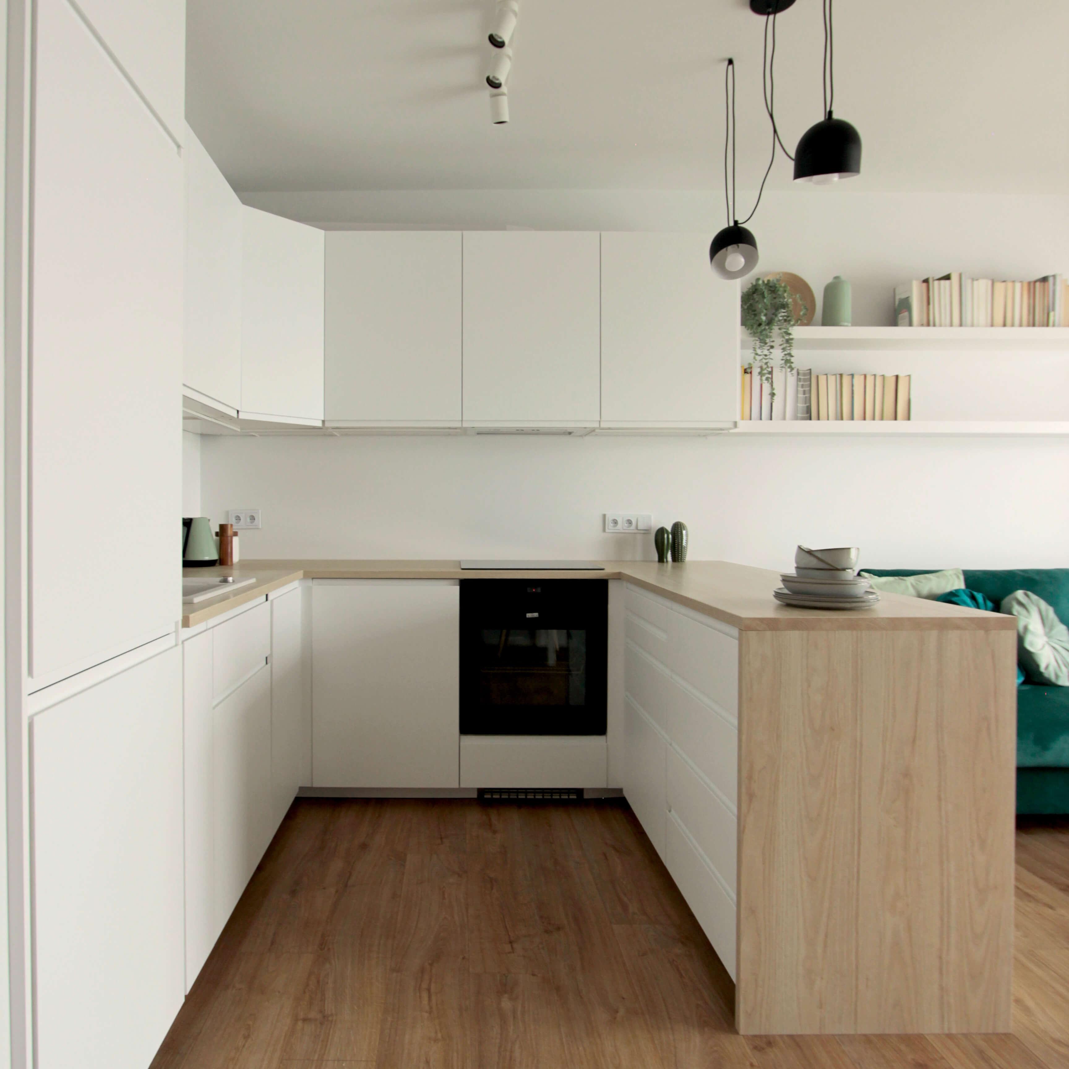 Projekt wnętrza mieszkania wraz z nadzorem nad realizacją. Aneks kuchenny w mieszkaniu 39 m2. Szafki kuchenne stają się znaczącym i widocznym elementem w strefie wypoczynkowej, dlatego warto zadbać o ich estetykę i spójność z resztą pomieszczenia. W tej kuchni zdecydowaliśmy się na fronty szafek bez uchwytów, żeby nie wprowadzać dodatkowych elementów do wnętrza.Z tego samego powodu wszystkie sprzęty AGD zostały zabudowane w szafkach. Dzięki temu kuchnia wygląda czysto i spokojnie.