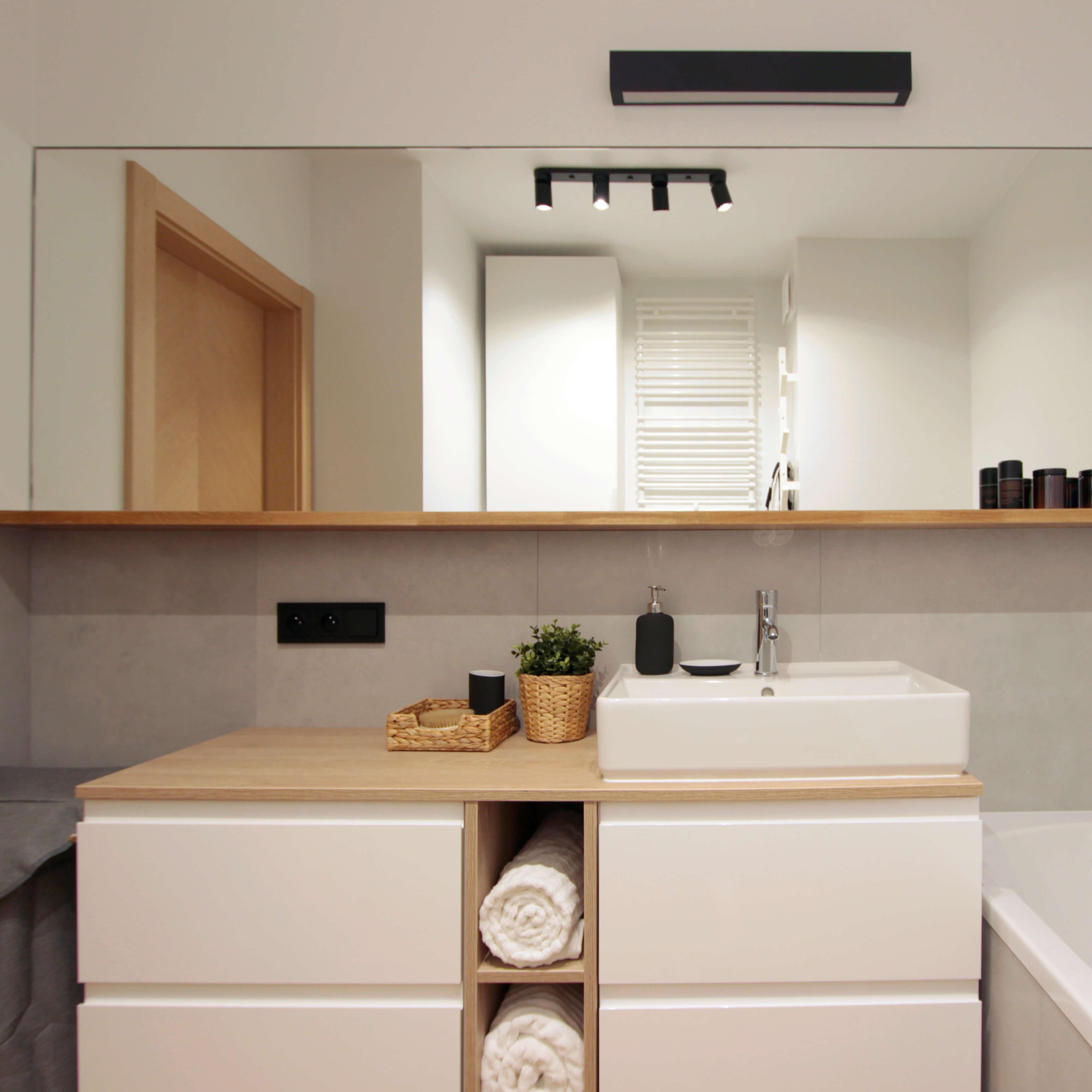 Projekt wnętrza mieszkania wraz z nadzorem nad realizacją. Sypialnia w mieszkaniu 39 m2. Odpowiednio wykorzystane lustra potrafią zdziałać we wnętrzach dużo dobrego. Ta łazienka dzięki lustrzanemu odbiciu zyskała optycznie wiele przestrzeni. Jasne, stonowane kolory ocieplają drewniane dodatki i podłoga.