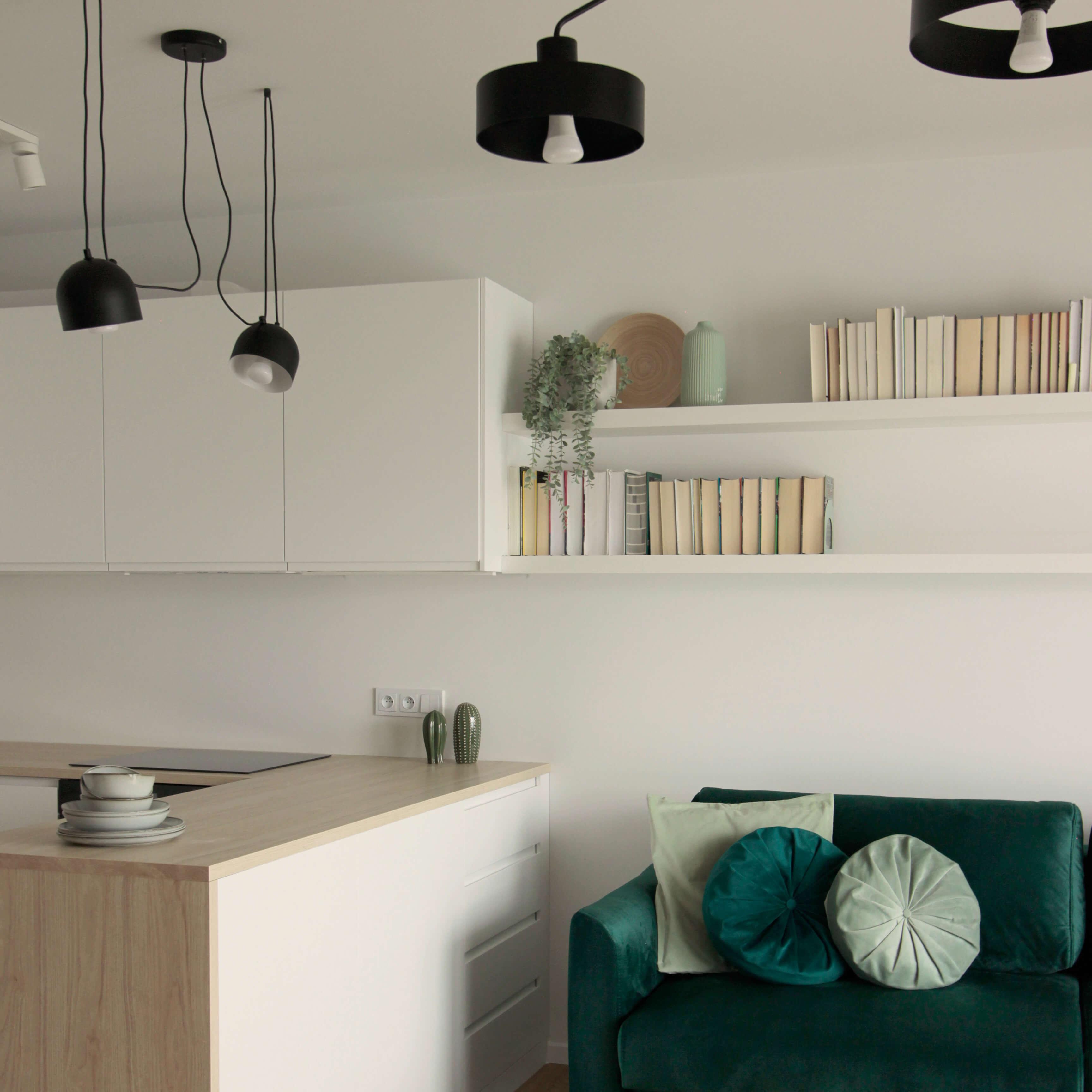 Projekt wnętrza mieszkania wraz z nadzorem nad realizacją. Salon w mieszkaniu 39 m2. Biały kolor jest podstawą tego wnętrza. Rozjaśnia i powiększa optycznie przestrzeń. Akcenty kolorystyczne są kontrastujące – czerń i piękna, ciemna, butelkowa zieleń. Dla ocieplenia mamy tu wiele drewnopodobnych elementów – podłoga, blaty, żaluzje okienne.
